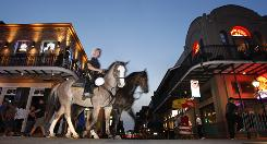 New Orleans mounted police patrol along Bourbon Street at the intersection of St. Louis Street in the French Quarter.