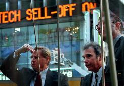 People in New York's Times Square peer anxiously through the window of the Nasdaq market.