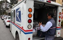 U.S. Postal Service letter carrier Anthony Ow sorts through mail in the back of his delivery truck July 30, 2009, in San Francisco.