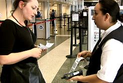 An American Airlines agent, right, prints a boarding pass from a handheld computing device called a YADA (Your Assistance Delivered Anywhere). To prevent long lines at check-in counters and self-service kiosks, the carrier began experimenting with the device.