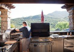 Stephen Hundley loads a homemade pizza into his outdoor artisan pizza oven at his home in Poway, Calif. Hundley cooks outside 3-5 days per week.