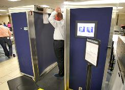 Dave Couts, a program analyst for the Transportation Security Administration, demonstrates how to stand in the new body-scanning machine at Sky Harbor International Airport in Phoenix. Some fliers are uncomfortable being scanned by the machines.