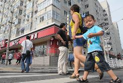 Pedestrians make their way across a crosswalk on a busy street in front of KFC in Beijing. Yum Brands has added more than 1,800 restaurants in China since 2005.