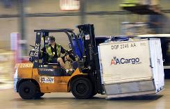 A fork lift moves a cargo container at the American Airline cargo processing warehouse at Dallas-Fort Worth International Airport in Grapevine, Texas. Airlines are buying new machinery to meet an Aug. 1 deadline to begin screening all cargo that goes on passenger planes.