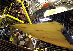 Scott Burleson, left, and Brett Goodman, work on making plywood at Columbia Forest Products in Old Fort, N.C.
