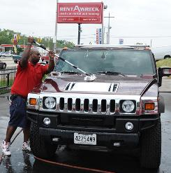 Michael Spencer washes a Hummer, one of the vehicles s available for rent at Rent-a-Wreck.
