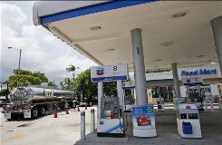 A gasoline tanker truck resupplies a Chevron gas station in North Miami Beach