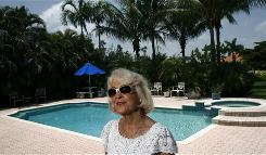 Marilyn Johnston of Plantation, Fla., by the pool she cleans herself to save money, says a modified mortgage through Wells Fargo saved her home.
