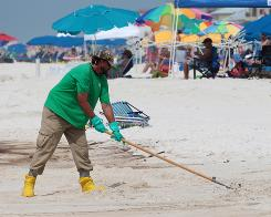 An oil cleanup worker rakes the sand in Orange Beach, Ala., as tourism suffers in the region.