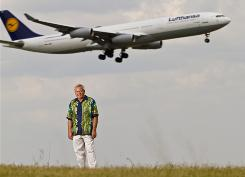 Tom Parsons, editor and publisher of BestFares.com, under a Lufthansa jet on final approach at Dallas/Fort Worth airport.