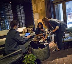 Kyle Gray, left, uses a tablet computer to check in Evangeline Wu, of Hong Kong, as Angela Ortiz serves her a cup of tea at Andaz in New York.