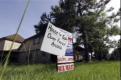 An owner's sign stands next to a real estate agent's for sale sign noting a reduced home price in Houston recently.