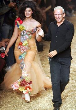 This Oct. 4, 2005 file photo shows French fashion designer Jean-Paul Gaultier, right, taking the catwalk with model Crystal Renn at the end of the presentation of his Spring/Summer ready to wear 2006 show in Paris.