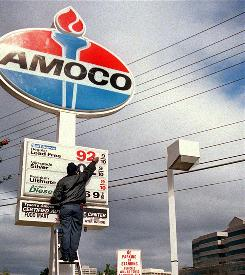 A worker at an Amoco station in Vienna, Va., changes advertised gasoline prices March 17, 2000.