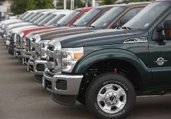 2011 Ford F-350 pickups are featured at a dealership in the west Denver suburb of Lakewood, Colo. Auto sales rose in July from a year ago.