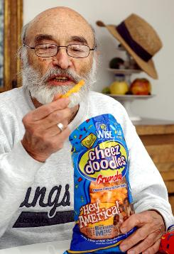 Morrie Yohai, inventor of Cheez Doodles, pulls one of the snacks out of a bag at his home in Kings Point, N.Y. in January 2005. Yohai died July 27, 2010, at his Long Island home in Kings Point at the age of 90.
