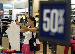 In this July 27, 2010 photo, a shopper looks at discounted clothing in an Aeropostale store in Paramus, N.J.