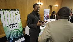 In this July 20, 2010 photo, Cedric James, admissions director with MyComputerCareer.Com meets prospective job applicants at a job fair in Plano, Texas.