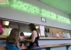 Nichole Caldwell, of Wilmington, Del., cashes a check at United Check Cashing in Wilmington with daughter Alyssa Todd, 10. 