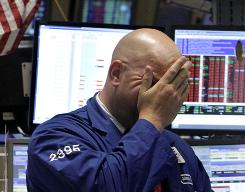 Specialist John Urbanowicz rubs his eyes as he works on the floor of the New York Stock Exchange on Wednesday as stocks tumbled as investors around the world took a bleaker view of the U.S. economy.