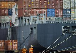 This Aug. 5, 2010 photo shows workers near a loaded container ship at the Tianjin port in China.