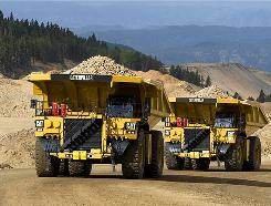 Caterpillar 793F mining trucks loaded on mine site haul their loads.