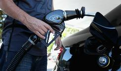A customer prepares to pump gas into his car at a Chevron gas station August 13, 2010 in San Rafael, Calif.