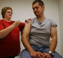 Carolyn Stefanski, gives a flu shot to Nicholas Sarakas at Saint Louis University.