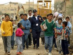 Iraqi students walk with Cassandra Nelson of Mercy Corps near a water supply project in 2003.