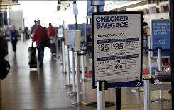 An American Airlines sign listing the fees for checked baggage is shown, at Seattle-Tacoma International Airport in Seattle. 