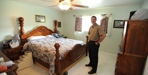 Marshall Hill stands in his rebuilt master bedroom. Flooding after Hurricane Katrina damaged his home.