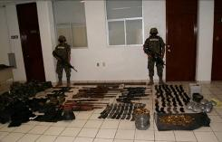 Mexican sailors guard weapons seized after a gun fight between the navy and a drug cartel after the killing Tuesday of 72 migrants in eastern Mexico.