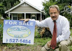 Realtor Joe Bell poses outside one of his properties in St. Petersburg, Fla. Mortgage rates have sunk to levels not seen in more than a half-century but brokers and lenders report not a flood but a trickle of customers.
