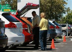 Annie Ellicott looks at a new Toyota with salesman Kapone Molina at Toyota of Marin in San Rafael, Calif.