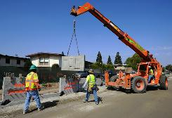 Construction workers move a piece of concrete wall with a crane as work continues on the first phase of the Exposition Light Rail Transit Line (Expo Line) that will connect downtown Los Angeles and Culver City, Calif. The state of California has been given over $3.7 billion in stimulus to address transportation and infrastructure problems.