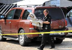 Lufkin, Texas, Police technician Debra Walsh carries a baby seat from a vehicle in which a 3-month-old was found dead on Aug. 24.