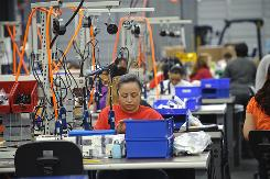 Workers assemble hair irons at Houston factory for Farouk Systems.