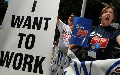 "Americans hold up ""I want to work"" signs as they join a protest of several thousand people demanding jobs outside City Hall in Los Angeles on August 13, 2010."