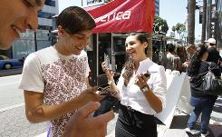 Virgin America's Amanda Wood hands out promo codes for a two-for-one deal to Peter Benke, left, and Matt Littrell on Aug. 31 in Los Angeles.