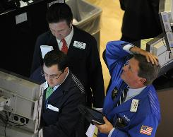 Traders on the floor of the New York Stock Exchange look at stocks during the final minutes of trading May 6, 2010 as the Dow lost almost 1,000 points before recovering to a loss of 505 .
