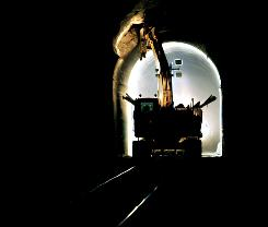 In this photo taken March 23, 2010, workers chip away at the ceiling of a tunnel that was built in 1904 in Logan, W. Va., to widen it for double-stacked freight trains.