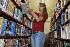 Brittany Wolfe, a 2010 graduate, checks old textbooks at the UCLA Powell Library Building in Los Angeles. Wolfe saved money by checking out textbooks, not buying them.