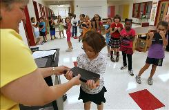 Ann Birrell hands out Dell laptops to her second-graders at Chandler Oaks Elementary School in Round Rock, Texas. While the company is focusing on business customers, it still has a major presence in education through its Connected Classroom program.