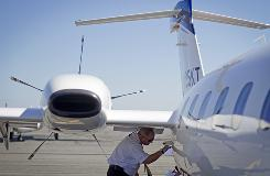 Piaggio America pilot Grant Spigener checks a panel on the P180 Avanti II turboprop business jet before a flight from Teterboro, N.J., to Nantucket, Mass. The company, led by CEO John Bingham, right, is trying to get business travelers to consider using private jets as an alternative to flying commercial.