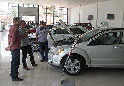 Mehdi Majeed, left, helps buyers at a Chrysler dealership in Baghdad. Traditionally, rich Iraqis have bought homes and cars outside Iraq, but that's changing.