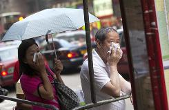 Commuters hold handkerchiefs to their faces as they wait for a bus in a shopping district in Hong Kong on May 8.