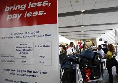 A sign is posted stating new fees for carry-on baggage by Spirit Airlines at the Fort Lauderdale-Hollywood International Airport in Fort Lauderdale
