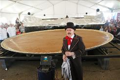Ringmaster Vernon Bergman reveals the weight of a 20-foot wide, 3,699-pound pumpkin pie baked in New Bremen, Ohio, on Saturday Sept. 25, 2010. It will be the worlds largest once certified by Guinness World Records. The massive pie took over thirteen hours to bake in a specially made oven. The New Bremen Giant Pumpkin Growers also made the previous world record for a Pumpkin Pie in 2005 with one that measured 12 ft wide and weighed 2,020 pounds.