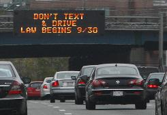 A sign over the Massachusetts Turnpike in Boston on Friday alerts motorists to a new state law banning texting while driving.
