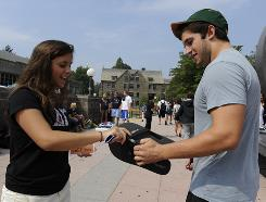 Villanova University junior Courtney Chupka (left) of Chatham, N.J., hands a pair of free American Eagle Outfitters flip-flops to fellow student Nicholas Benenati, a sophomore from Miami. Chupka was one of a team of Villanova students dressed in matching T-shirts to promote American Eagle Outfitters on campus.